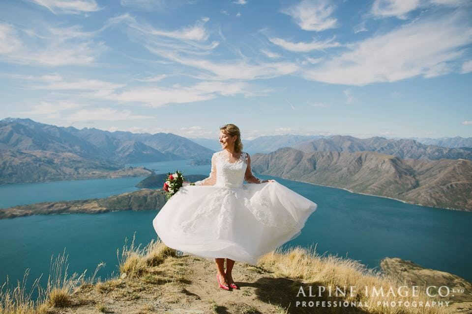 Stunning Alison in Charlotte by House of Mooshki showing off her dress on top of a mountain in New Zealand. Image by Alpine Image Company.