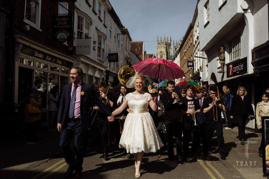 Sally at her New York Brass Band wedding in York in her apricot coloured tea-length Sarah dress by House of Mooshki. Images by Toast of Leeds