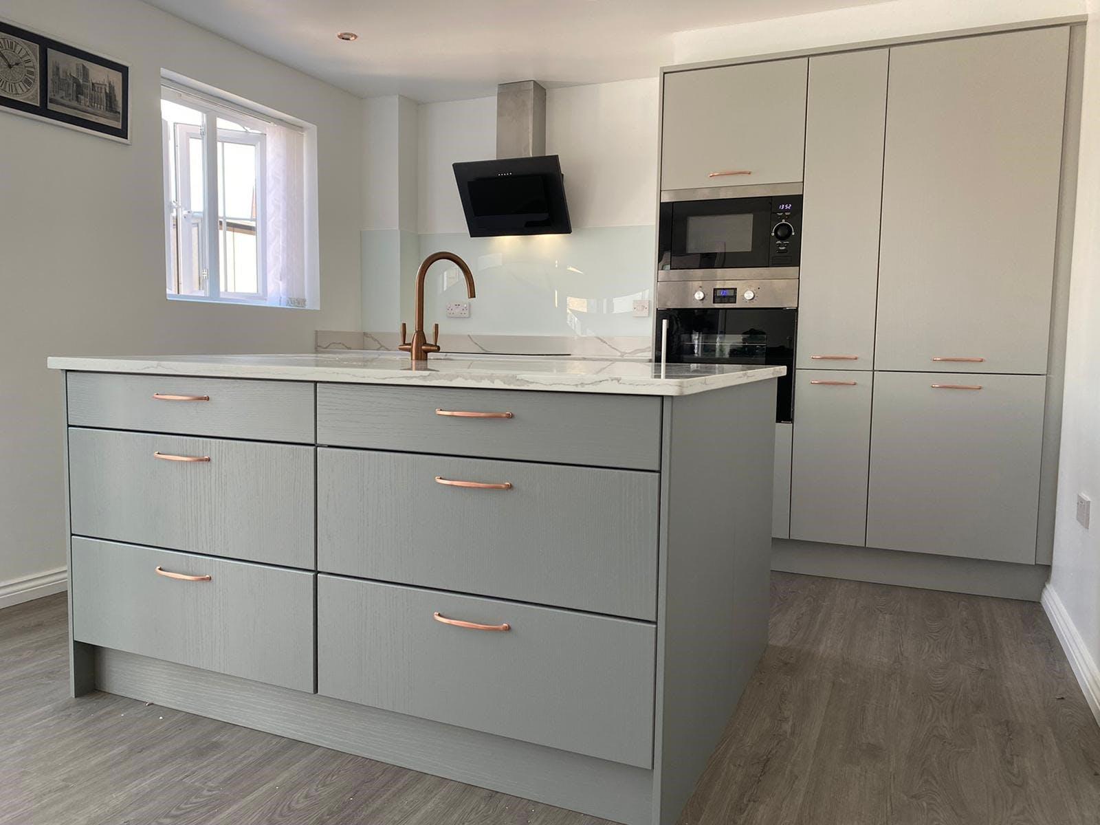 Calacatta Quartz Worktop On Grey Slab Kitchen With Copper Handles and Glass Splashback