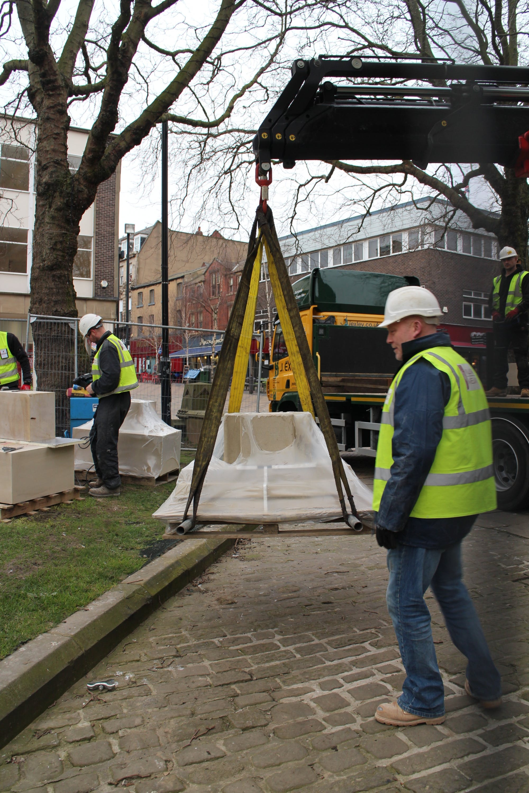 The crane sets to work lifting the base stones into place.
