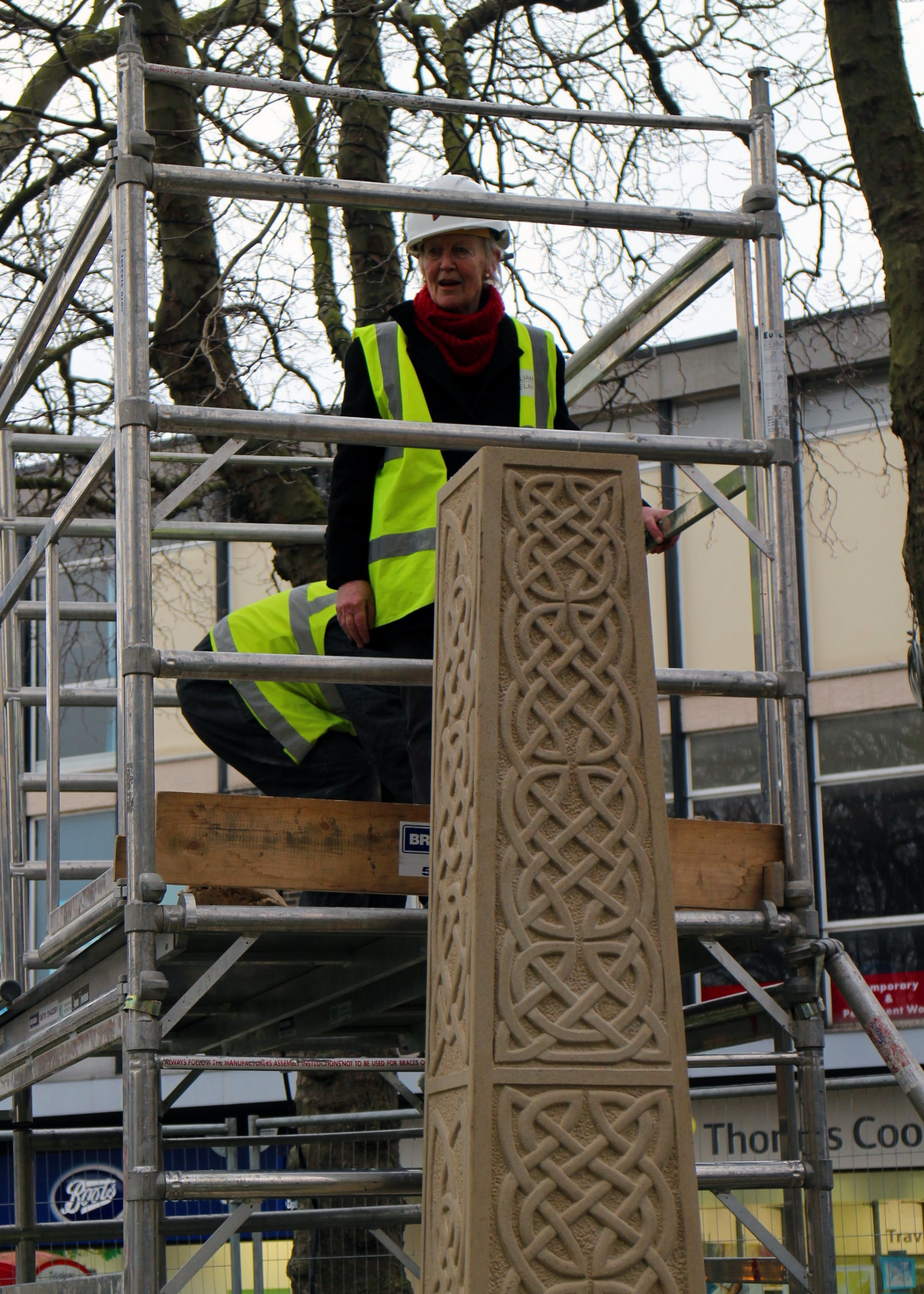 Celia climbs up the scaffolding to cement the cross in place