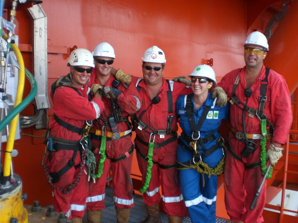 Ila Glennie on the side of a ship in Angola, working with a team of South African technicians.