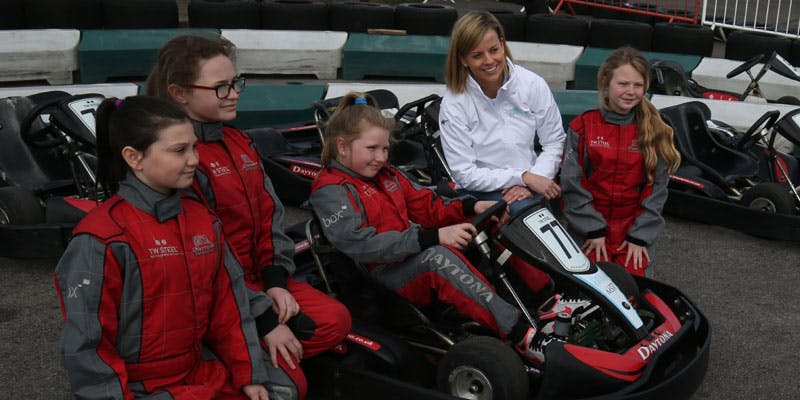 Formula 1 driver Susie Wolff with a group of girls in racing cars