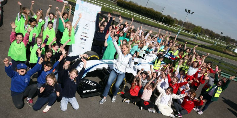 Formula 1 driver Susie Wolff with a large group of girls